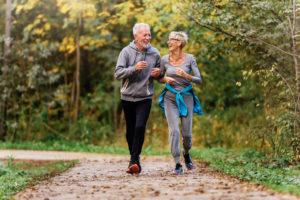 Active Senior Couple jogging in park