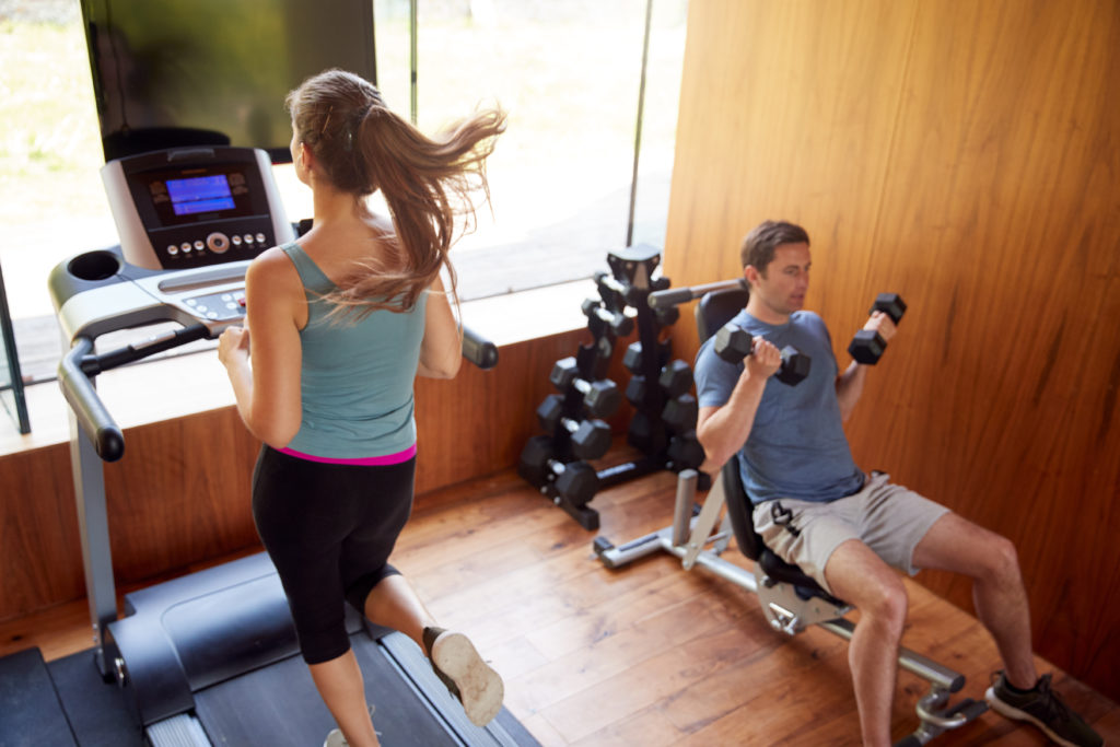 Couple In Home Gym Exercising With Weights And Using Running Machine