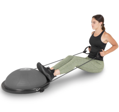 woman doing seated rows with a band attached to gray balance trainer