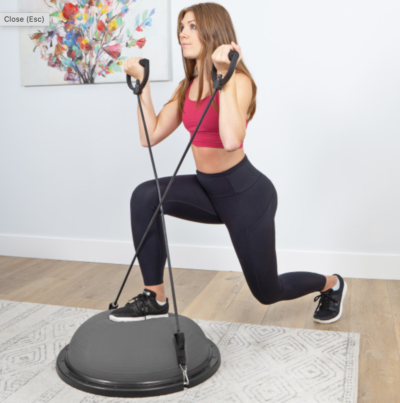 woman doing lunges and curls with an exercise band on a gray balance trainer
