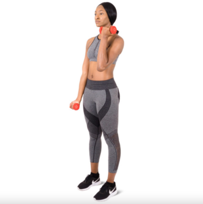 woman doing alternating curls with a pair of red 3 lb. neoprene dumbbells