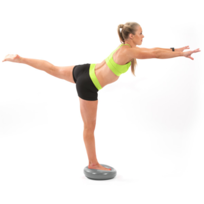 Woman balancing on one leg on balance disc with one leg behind and arms extended out in front