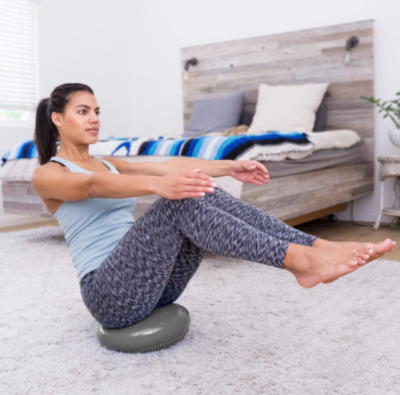 woman sitting with legs raised on grey balance disc