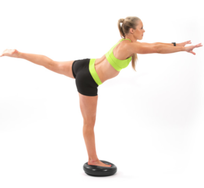 woman balancing on one leg on black balance disc with leg extended out behind and arms extended in front
