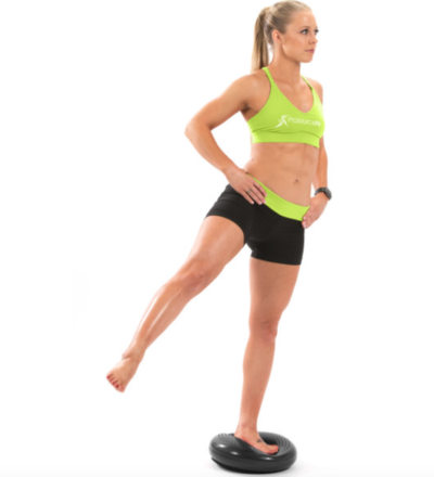 woman balancing on one leg with leg extended out to the side on a black core balance disc