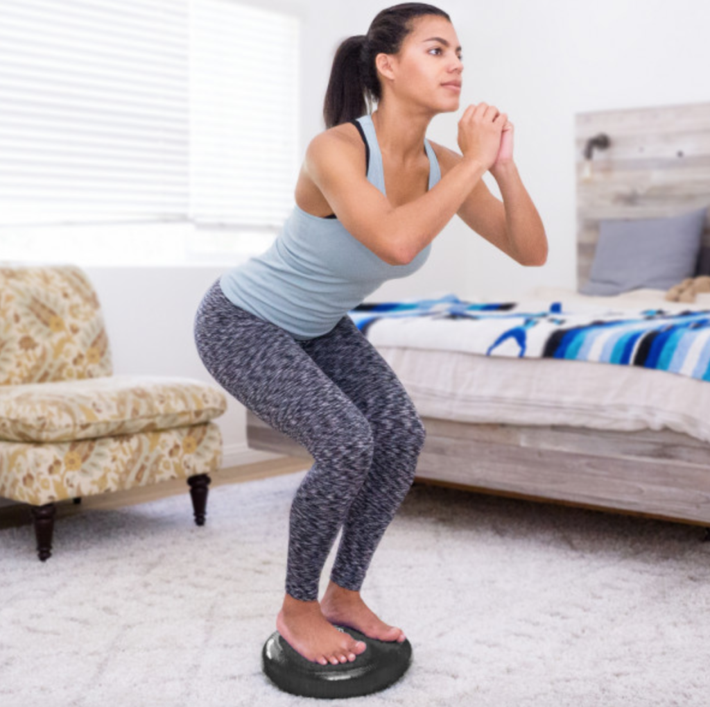 woman standing with knees bent on black core balance disc