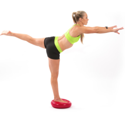 woman balancing on one leg on red core balance disc with leg extended out behind you and arms extended in front