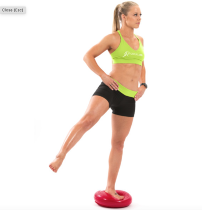 woman balancing on one leg on red core balance disc with leg out to the side