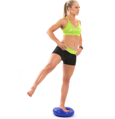 woman balancing on one leg on blue core balance disc with leg out to the side