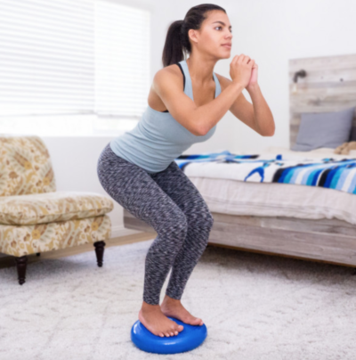woman standing on blue core balance disc in a squatting position