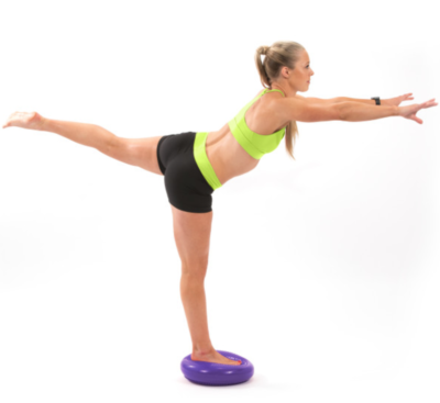 woman balancing on one leg on purple core balance disc with one leg extended behind her and arms reaching out in front of her