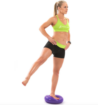 woman balancing on one leg with other leg out to side on purple core balance disc
