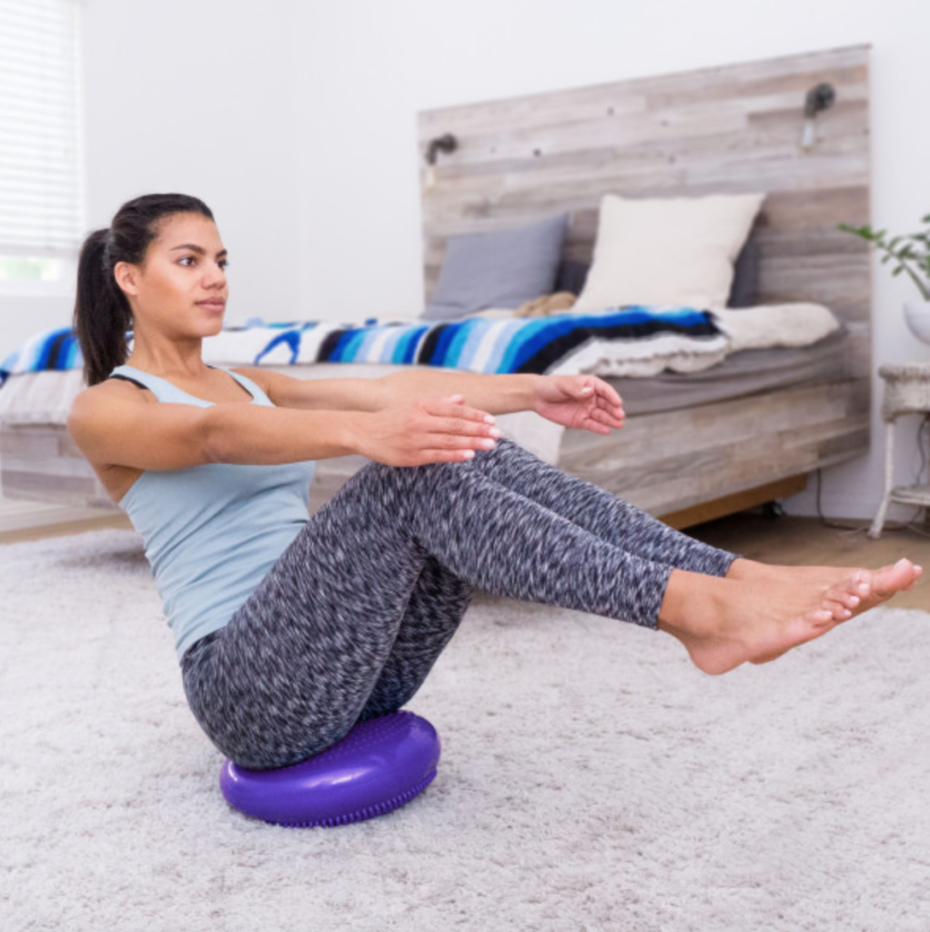 woman sitting on purple core balance disc with legs raised up to work her core