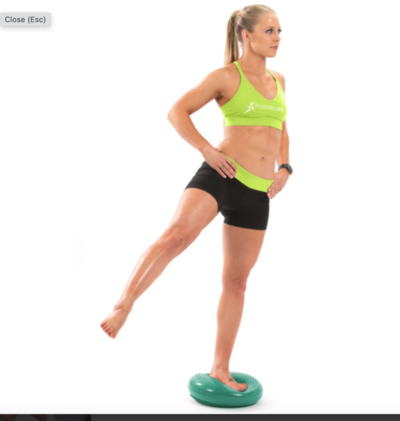 woman standing on one leg on green core balance disc with other leg extended out to side