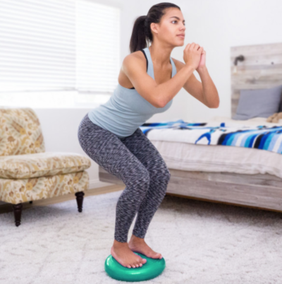 woman standing in a squat position on green core balance disc