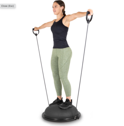 Woman doing lateral raises on black balance trainer