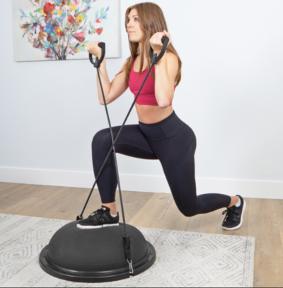 woman doing lunge and curl on black balance trainer
