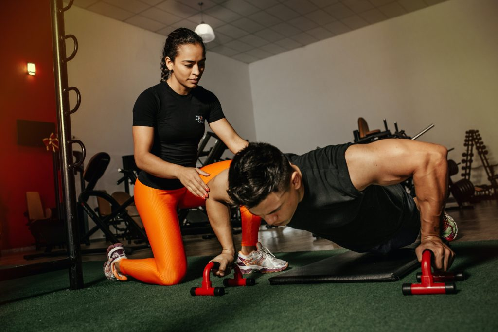 Female trainer training her client doing pushups