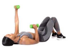 Woman lying on her back lifting a 4 lb. neoprene dumbbell